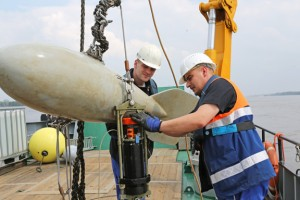 Mitarbeiter der Wasser- und Schifffahrtsverwaltung heben eine Messboje aus der Elbe