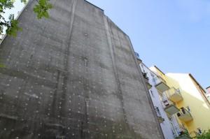 Die hellen Punkte auf dem Schwarzschimmelbefall sind die Dübel, mit denen die Dämmplatten auf dem Mauerwerk befestigt wurden.